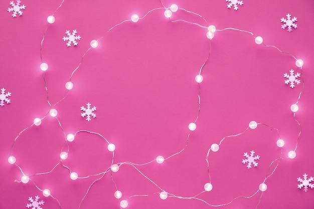Vista superiore laica piana del modello di natale o del nuovo anno fiocchi di neve di carta decorativi di celebrazione di festa di natale e ghirlanda delle luci festive su fondo rosa. sfondo colorato monocromatico vibrante alla moda.
