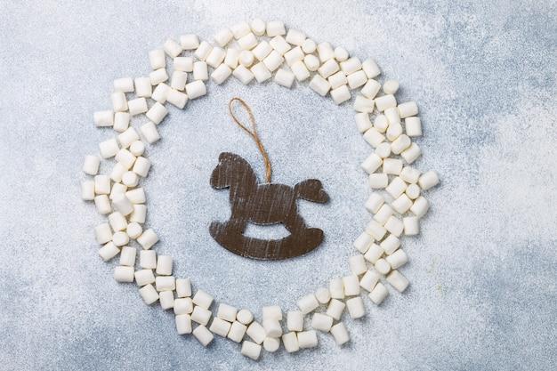 Vista superiore piana di natale o di capodanno con marshmallow e giocattolo di cavallo in legno rustico