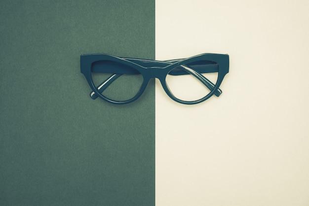 Vista superiore piatta laici, moderni occhiali blu su sfondo di carta pastello