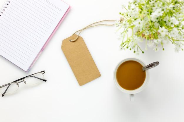 Vista superiore ufficio business desk.greeting carta, occhiali da sole, bel fiore bianco, caffè, notebook su scrivania bianca con spazio di copia.