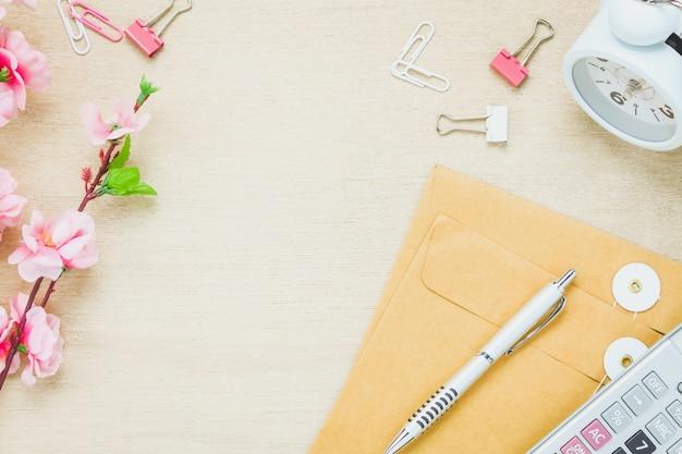 Vista superiore ufficio ufficio desk background.the penna lettera calcolatrice clip di orologio da fiore sullo sfondo della tabella di legno con spazio di copia.