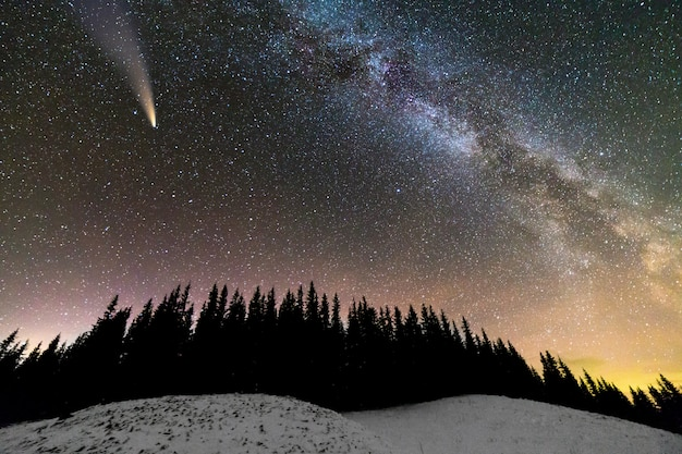 Vista surreale della notte in montagna con cielo nuvoloso blu scuro stellato e brillante cometa con coda leggera.