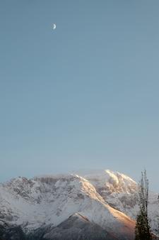 Vista verticale del paesaggio della natura di catena montuosa ricoperta neve contro chiaro cielo blu.
