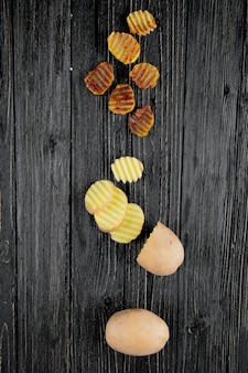 Vista verticale delle fette delle patatine fritte con il taglio e quelle intere su fondo di legno con lo spazio della copia