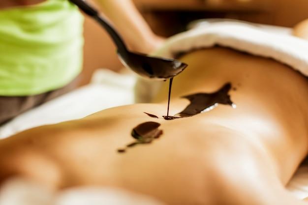 Visualizza la donna con un massaggio hot chocolate