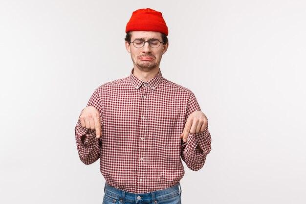Vita alta ritratto angosciato e turbato piagnucoloso giovane ragazzo sconvolto in berretto rosso, singhiozzando e facendo una smorfia triste come indicando guardando in basso con rimpianto o gelosia, lutto