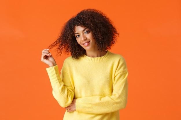 Vita alta ritratto impertinente e civettuola bella donna afroamericana rotolando il ricciolo nelle dita inclinando la testa e controllando qualcuno con sfacciato sorriso civettuolo, in piedi arancione