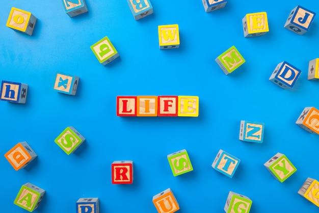 Vita, blocchi di alfabeto colorato superficie in legno su blu, piatto laici, vista dall'alto