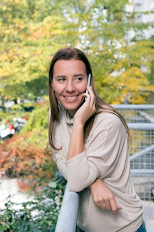 Vita di città giovane donna attraente con il telefono cellulare che parla all'aperto