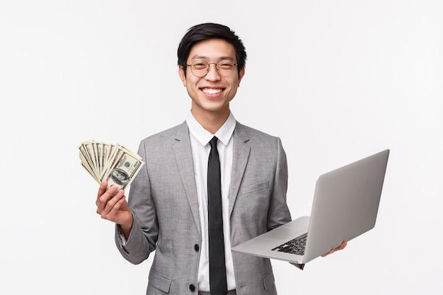 Vita di giovane uomo asiatico sorridente felice e piacevole in vestito grigio che tiene i dollari