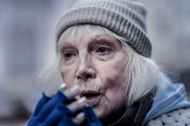 Vita difficile. ritratto di una cupa povera donna anziana che si rompe le mani mentre cerca di riscaldarsi