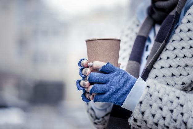 Vita in povertà. primo piano di un bicchiere di carta con monete nelle mani di una povera donna di età
