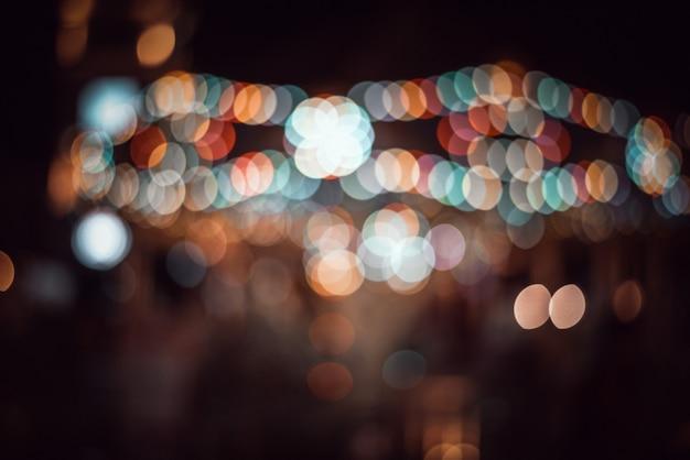 Vita notturna sfocata in città: automobili, persone e lampioni, stile retrò