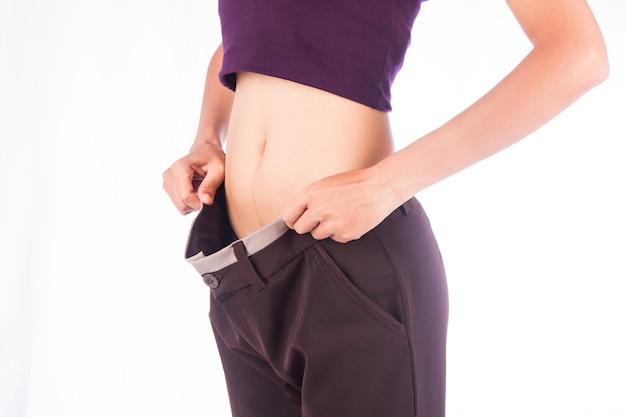 Vita sottile di donna di bellezza in grandi pantaloni, dopo che il peso è allentato