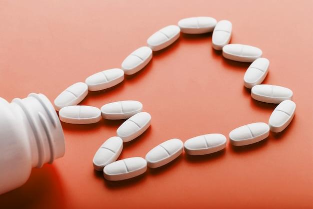 Vitamina di calcio sotto forma di un dente rovesciato da un barattolo bianco su un rosso.