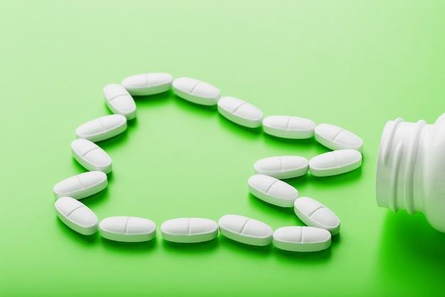 Vitamina di calcio sotto forma di un dente versato da un vaso bianco su un verde.