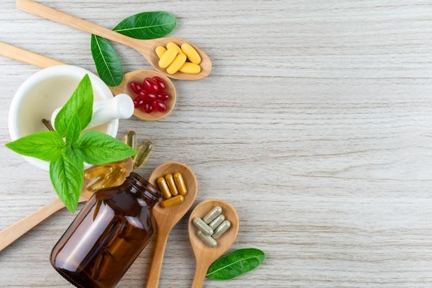 Vitamina e integratori organici naturali, foglia in mortaio sul concetto di legno del fondo, medicina e droga