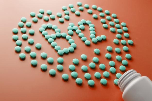 Vitamine b 12 a forma di cuore su un substrato rosso, versato da un barattolo bianco.