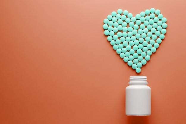 Vitamine b 12 su un substrato a forma di cuore rosso, versato da un barattolo bianco.
