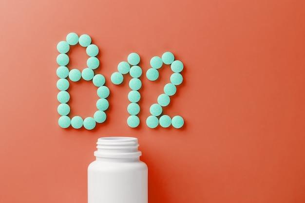 Vitamine b 12 su un substrato rosso, versato da un barattolo bianco.