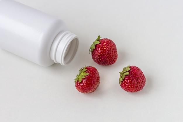 Vitamine fresche come fragole dalla bottiglia di pillola bianca della medicina.