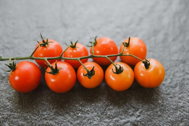 Vite di pomodoro rossa matura per cibo cotto sul tavolo nero. ramo di pomodori freschi sulla banda nera