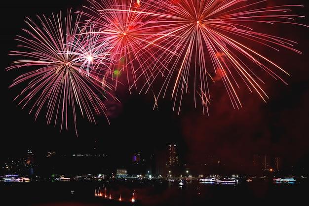 Vivaci fuochi d'artificio rossi che schizzano nel cielo notturno della città