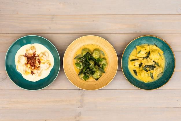 Vividi piatti di ravioli disposti in fila sul tavolo di legno