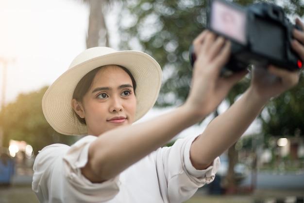 Vlog asiatico della registrazione della donna di viaggio del ritratto del selfie sulla macchina fotografica della ragazza turistica asiatica sul vlogging di vacanza della tailandia che parla sul flusso in diretta. destinazione turistica estiva