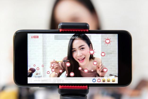 Vlogger asiatico di bellezza della donna che divide il video di tutorial di trucco sui media sociali
