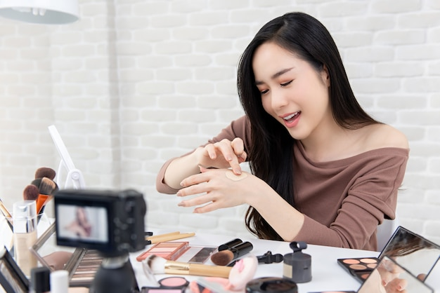 Vlogger asiatico di bellezza della donna che registra la rassegna cosmetica del prodotto di trucco con la macchina fotografica