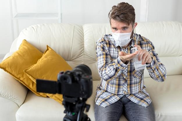 Vlogger che registra video a casa con disinfettante per le mani