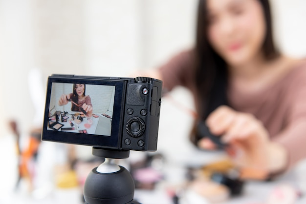 Vlogger di bellezza della donna che registra esercitazione cosmetica di trucco con la macchina fotografica