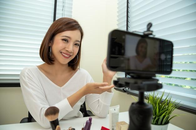 Vlogger di bellezza donna asiatica o blogger in diretta in diretta di tutorial trucco cosmetico