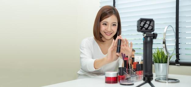 Vlogger o blogger di bellezza donna asiatica trasmissione live di clip tutorial tutorial trucco cosmetico tramite telefono cellulare e condivisione sul canale o sito web di social media, stile di vita di influencer e selfie che prendono immagini