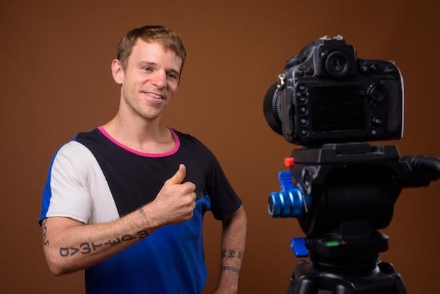 Vlogging uomo mentre indossa camicia blu contro il muro marrone