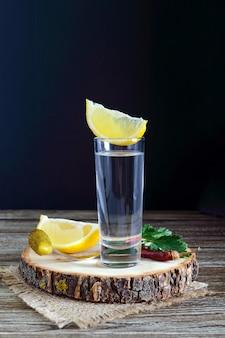 Vodka o tequila in bicchierini e in bottiglia con salsa di limone su fondo di legno rustico.