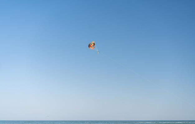 Vola con colorati paracadute in spiaggia