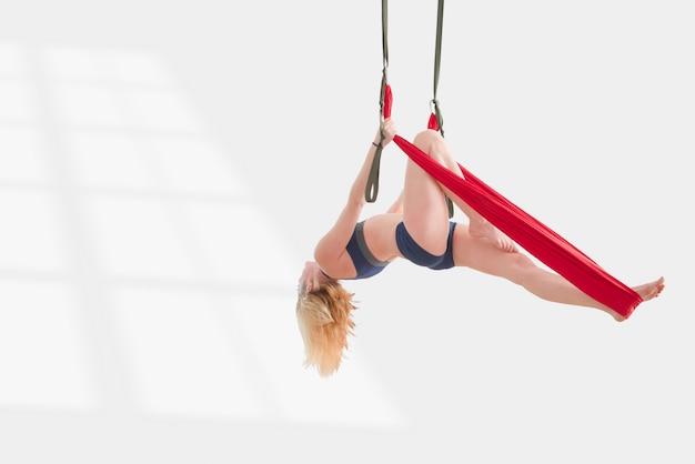 Vola yoga. la ragazza è impegnata nello yoga aereo su un'amaca. aula di loft bianco palestra allenamento fitness