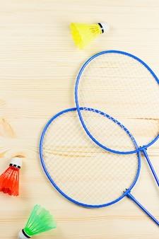 Volani colorati e racchette da badminton distesi sulla scrivania in legno