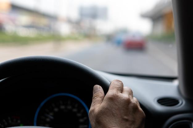 Volante della tenuta della mano dell'uomo anziano che guida sulla strada nel giorno pacifico, salute dell'anziano