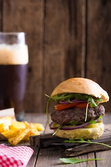 Volantino per hamburger. hamburger al formaggio con carne alla griglia, birra, insalata di rucola e anelli di cipolla.