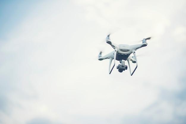 Volare drone fino a sfondo blu del cielo