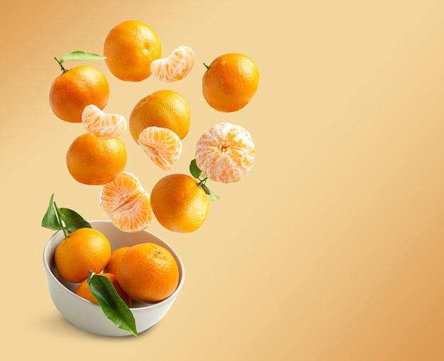 Volata dei mandarini isolata da fondo arancio con lo spazio della copia