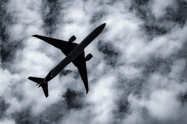 Volo commerciale della linea aerea sul cielo scuro e sulle nuvole lanuginose bianche.