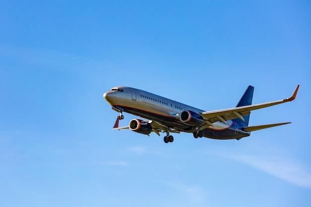 Volo dell'aereo passeggeri nei raggi del cielo blu al sole