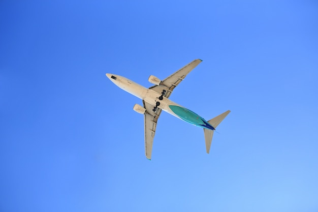 Volo dell'aeroplano sul cielo blu. visto dal basso.
