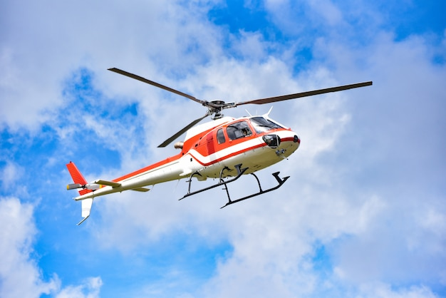 Volo dell'elicottero di salvataggio di elicottero sul cielo / elicottero rosso bianco della mosca su cielo blu con il giorno luminoso dell'aria della buona nuvola