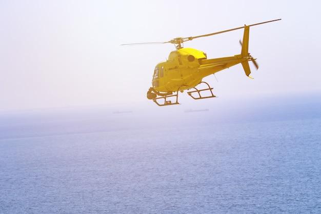 Volo giallo dell'elicottero, cielo blu e nuvole bianche
