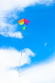 Volo variopinto dell'aquilone nel cielo blu del fondo del vento